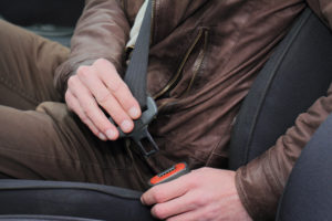 Driving safety concept. Man fastening seat belt in car close up